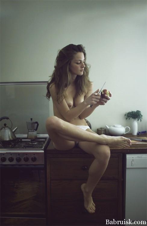 Голая девушка чистит яблоко